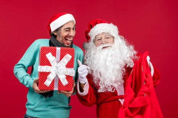Vista frontal de santa claus con hombre sacando el presente de la bolsa en rojo emociones de navidad color rojo