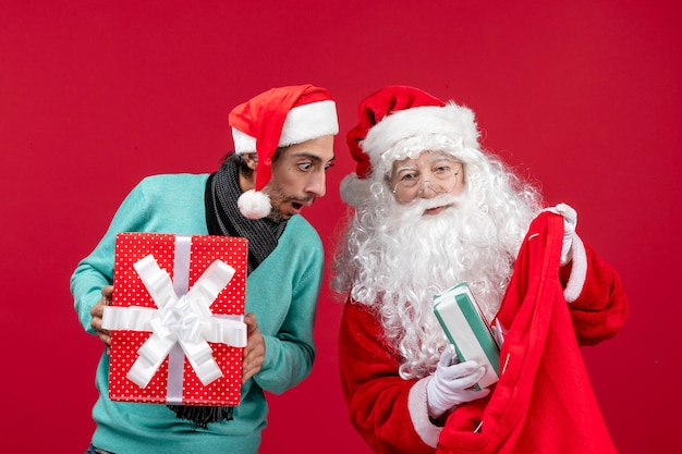 Vista frontal de santa claus con hombre sacando regalos de la bolsa en la emoción de navidad de regalo rojo