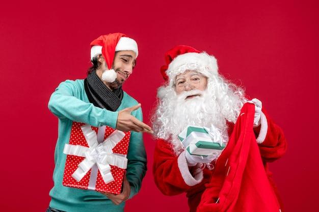 Vista frontal de santa claus con hombre sacando regalos de la bolsa en el escritorio rojo regalo emoción de navidad rojo