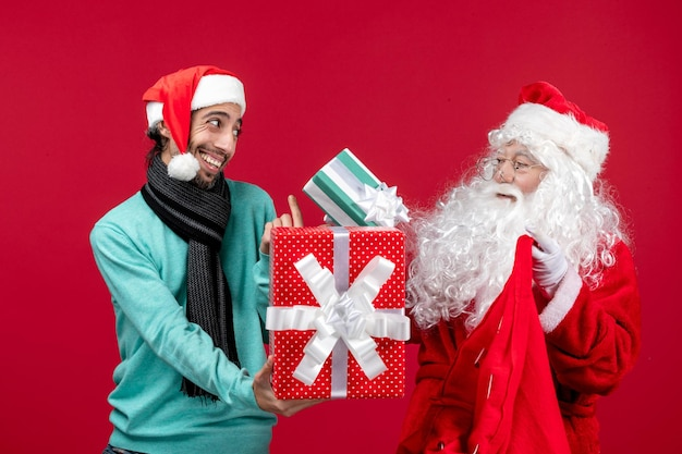 Vista frontal de santa claus con hombre sacando regalos de la bolsa en el piso rojo regalo emoción de navidad rojo