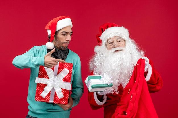 Vista frontal de santa claus con hombre sacando regalos de la bolsa en regalos rojos emoción de navidad rojo