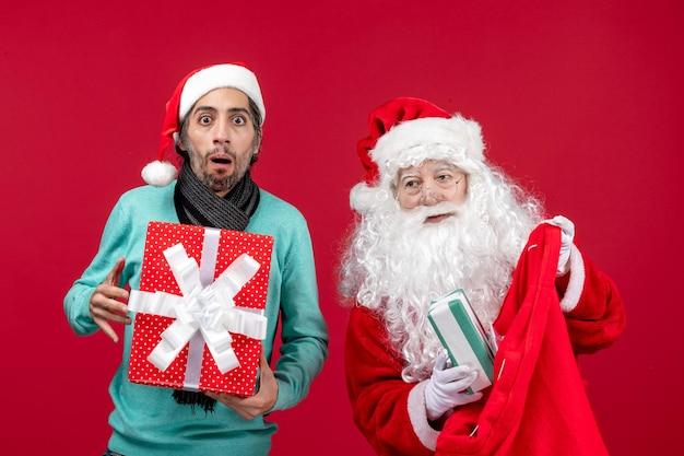 Vista frontal de santa claus con hombre sacando regalos de la bolsa en rojo regalo rojo emoción de navidad