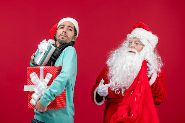 Vista frontal de santa claus con hombre sacando regalos de bolsa en rojo rojo regalo emoción de navidad