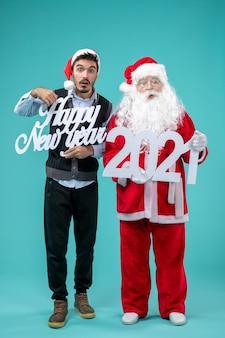 Vista frontal de santa claus con hombre sosteniendo feliz año nuevo y 2021 tableros en pared azul