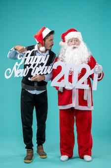 Vista frontal de santa claus con hombre sosteniendo feliz año nuevo y bolsas de compras en la pared azul