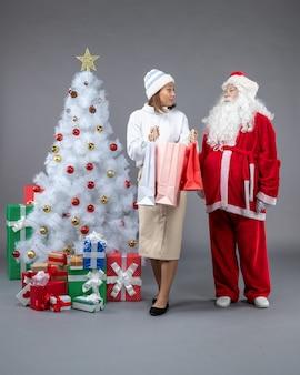 Vista frontal de santa claus con joven alrededor del árbol de navidad y regalos en la pared gris