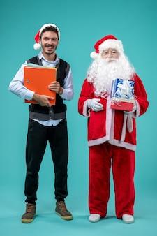 Vista frontal de santa claus con joven y regalos navideños en la pared azul