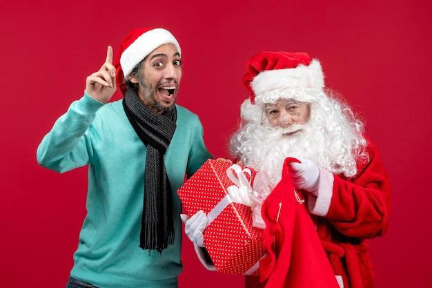 Vista frontal de santa claus con macho sacando el presente de la bolsa en color rojo de emoción navideña de vacaciones