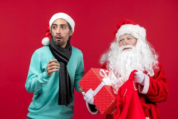 Vista frontal de santa claus con macho sacando el presente de la bolsa en color rojo de vacaciones de emoción de navidad
