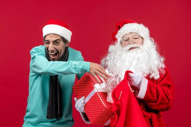 Vista frontal de santa claus con macho sacando el presente de la bolsa en el escritorio rojo color de vacaciones de emoción de navidad