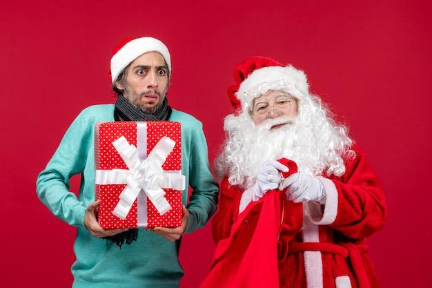Vista frontal de santa claus con macho sacando el presente de la bolsa en el escritorio rojo emoción de navidad color rojo
