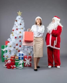 Vista frontal de santa claus con mujer joven alrededor del árbol de navidad y presenta en la pared gris