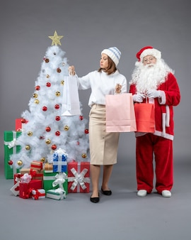 Vista frontal de santa claus con mujer joven alrededor del árbol de navidad y regalos sobre fondo gris
