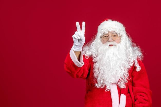 Vista frontal de santa claus con oso blanco clásico y ropa roja en un año nuevo de navidad rojo