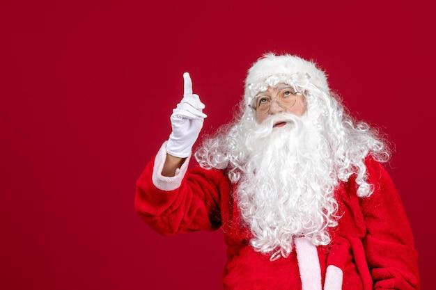 Vista frontal de santa claus con oso blanco clásico y ropa roja en vacaciones rojas de navidad