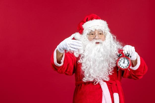 Vista frontal santa claus sosteniendo el reloj en la emoción de año nuevo de vacaciones de navidad roja