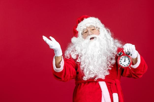 Vista frontal de santa claus sosteniendo el reloj en la emoción de navidad de escritorio rojo