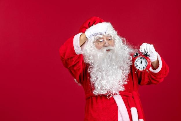 Vista frontal de santa claus sosteniendo el reloj en una emoción de vacaciones de navidad roja