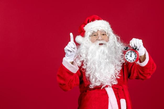 Vista frontal santa claus sosteniendo el reloj en el escritorio rojo emoción de año nuevo de navidad