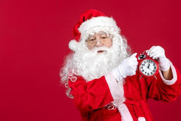 Vista frontal de santa claus sosteniendo el reloj en el escritorio rojo vacaciones de navidad