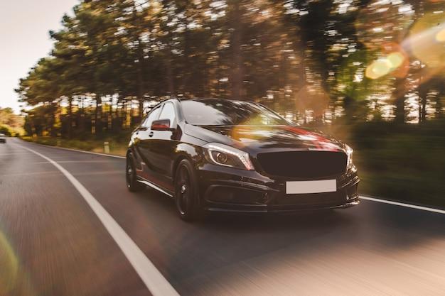 Vista frontal de un sedán de lujo negro en la carretera.