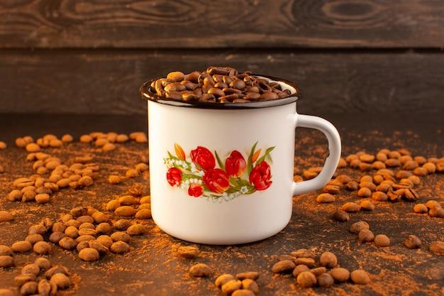 Una vista frontal de las semillas de café marrón dentro del recipiente en la semilla de café marrón