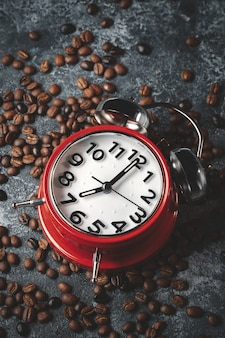 Vista frontal de las semillas de café marrón con superficie oscura de relojes rojos