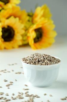 Una vista frontal de semillas de girasol saladas dentro de un plato blanco aislado junto con girasoles en el blanco