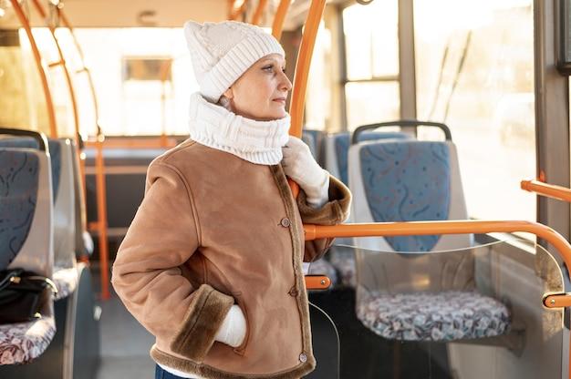 Vista frontal senior femenino montando autobús
