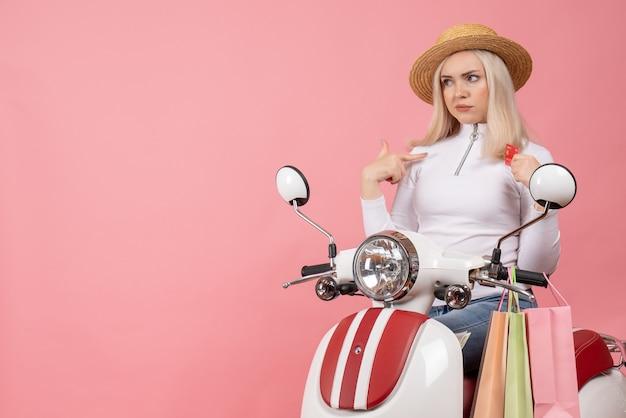 Vista frontal señorita en ciclomotor con bolsas de compras en pared rosa