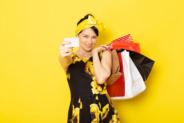 Una vista frontal señorita en vestido de flores amarillo-negro diseñado con vendaje amarillo en la cabeza con paquetes de compras en el amarillo