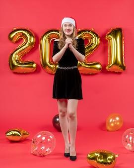 Vista frontal señorita en vestido negro deseando globos en rojo