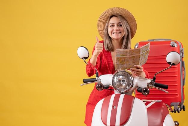 Vista frontal señorita en vestido rojo sosteniendo mapa dando pulgar hacia arriba cerca de ciclomotor