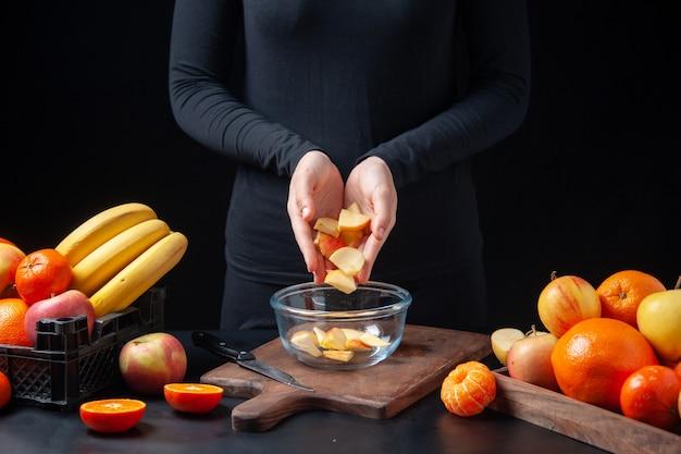 Vista frontal del ser humano poniendo rodajas de manzana fresca en un tazón de vidrio sobre la tabla de cortar en la mesa de la cocina