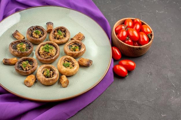 Vista frontal de setas cocidas dentro de la placa con tomates sobre fondo oscuro plato setas cena cocinando comida
