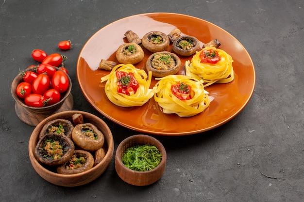 Vista frontal de setas cocidas con pasta de masa en la cena de plato de comida de mesa oscura