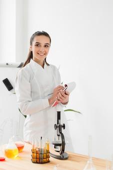Vista frontal de smiley científico femenino en bata de laboratorio con bloc de notas