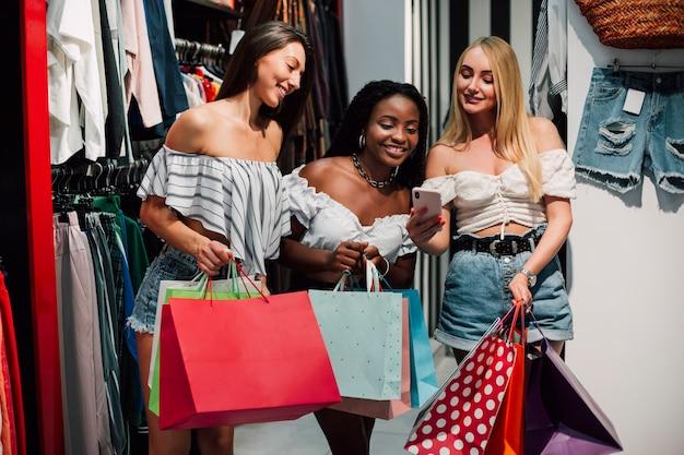 Vista frontal smiley mujeres mirando móvil