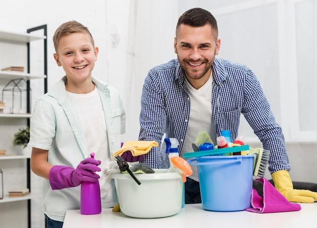Vista frontal de smiley padre e hijo posando con productos de limpieza