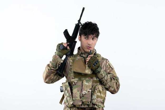 Vista frontal del soldado en camuflaje con ametralladora pared blanca