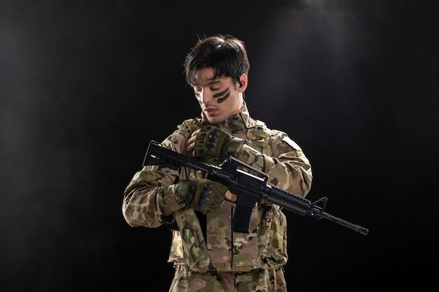 Vista frontal del soldado en camuflaje con ametralladora pared oscura