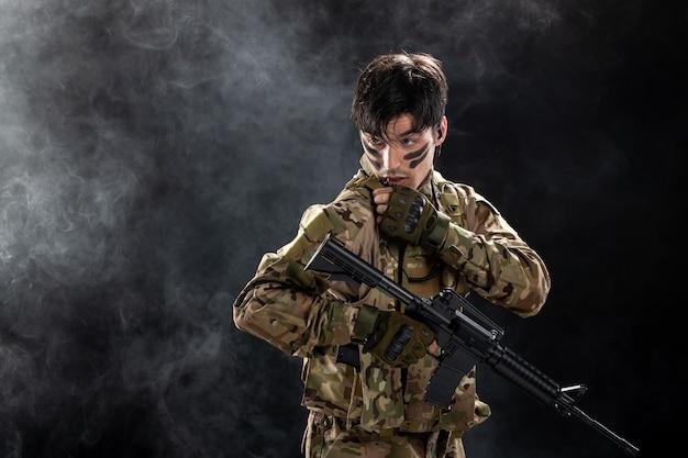 Vista frontal del soldado de camuflaje con rifle en pared negra