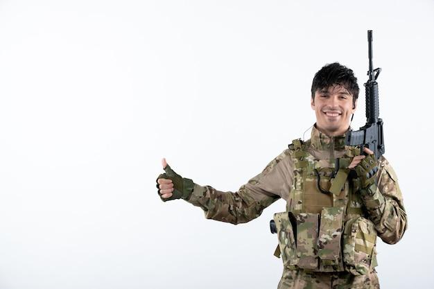 Vista frontal del soldado masculino con ametralladora en pared blanca de camuflaje