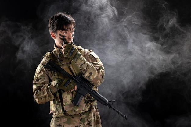 Vista frontal del soldado masculino con ametralladora con walkie-talkie pared negra