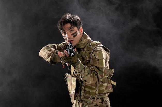Vista frontal del soldado masculino en camuflaje con el objetivo de rifle en la pared oscura