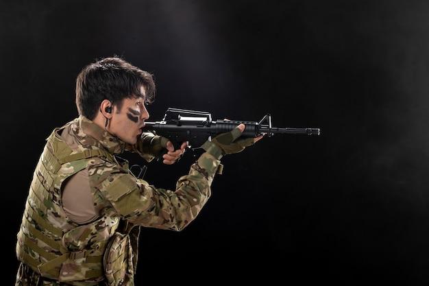 Vista frontal del soldado masculino luchando con rifle en una pared oscura