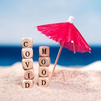 Vista frontal de la sombrilla en la playa con covid humor