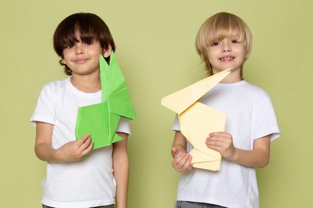 Una vista frontal sonriendo niños felices en camisetas blancas con coloridos juguetes de papel en el espacio de color piedra