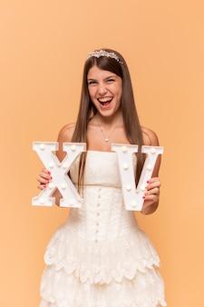 Vista frontal sonriente adolescente celebrando su quinceañera