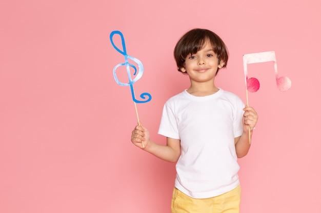 Una vista frontal sonriente adorable niño con carteles coloridos en camiseta blanca en el escritorio rosa